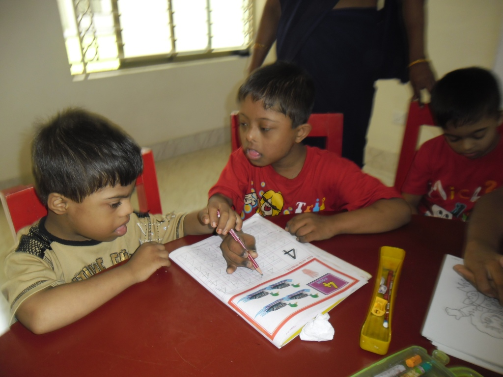 A student teaching another How to write.